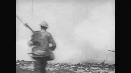 UNITED STATES: 1910s: view from behind as soldiers run across field into battle. Soldiers fire from trench.