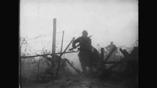 UNITED STATES: 1910s: soldiers run through fence. Soldiers run into trench. Gun fires on soldiers. Soldiers surrender in trench.