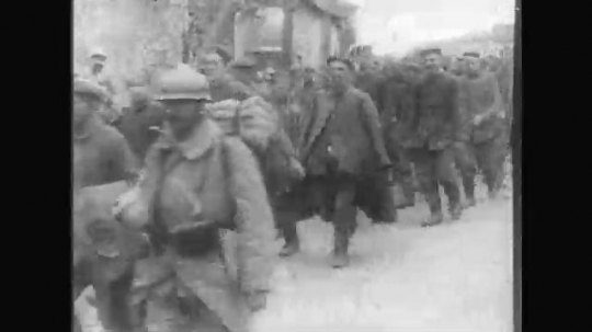 UNITED STATES: 1910s: soldiers walk along road. Soldiers stand behind fence Prisoners of war.