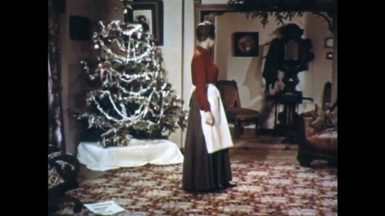 UNITED STATES: 1950s: lady takes off apron in room. Lady speaks up stairs.