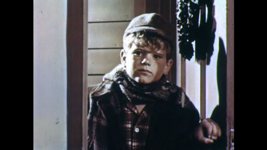 UNITED STATES: 1950s: boy looks through door. Boy smiles