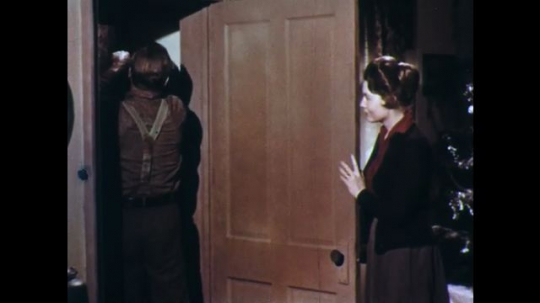UNITED STATES: 1950s: man hides sledge in cupboard. Man talks to lady.