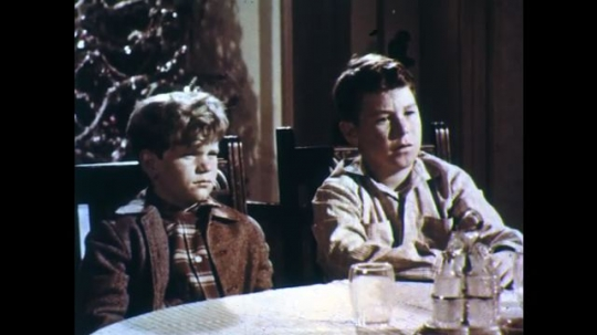 UNITED STATES: 1950s: boys listen. Man speaks with boy. Boy reads from book