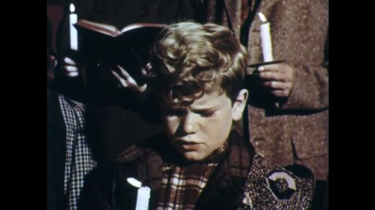 UNITED STATES: 1950s: boy sings in church. Boy holds candle