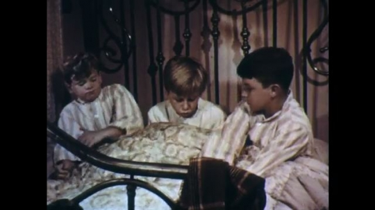 UNITED STATES: 1950s: three boys sit and talk in bed. Boys climb out of bed. Boys put on jackets.