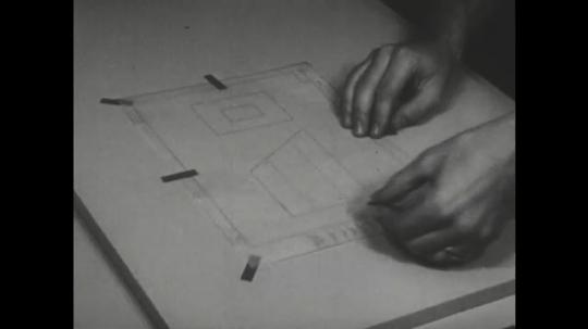 UNITED STATES: 1960s: fingers stick tape around paper edges.