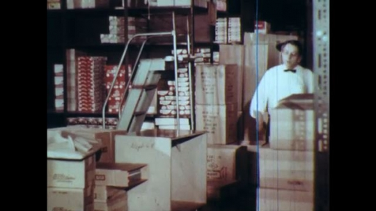 UNITED STATES: 1960s: man takes off shoe in store room. Man talks to employee. Man shows himself after hiding