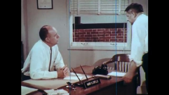 UNITED STATES: 1960s: men talk at desk in office. Man sits at desk with colleague. Men argue in office.