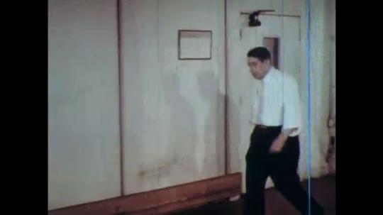 UNITED STATES: 1960s: men talk at desk in office.
