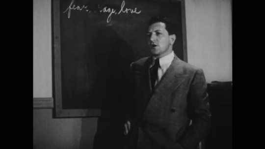 UNITED STATES: 1950s: Teacher speaks to students. Girl speaks in class. Man stands by box.