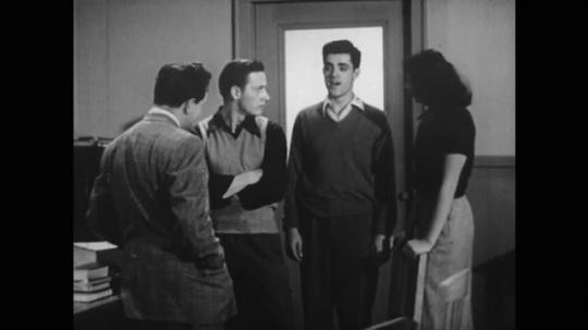 UNITED STATES: 1950s: teacher speaks with students in classroom. Teacher walks to desk. Model of brain. Label of thalamus.