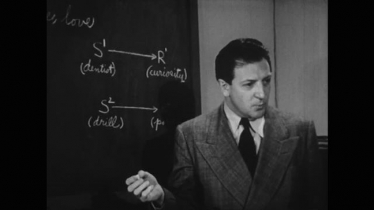 UNITED STATES: 1950s: man by chalk board speaks. Man draws dotted line on chalk board.