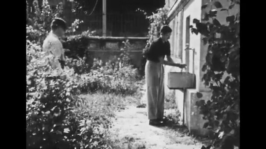 UNITED STATES: 1940s: man washes hands in outdoor sink. Man points stick at wall