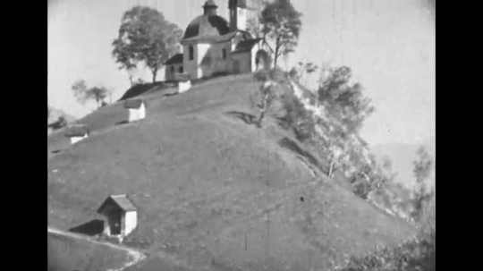 UNITED STATES: 1940s: church on hill. Man paints landscape picture.