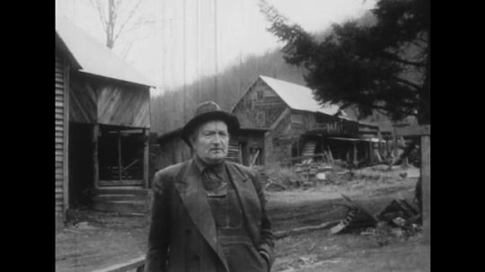 UNITED STATES: 1950s: man talks to camera by wooden shacks