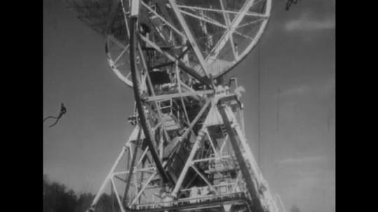 UNITED STATES: 1950s: view up towards satellite communication tower and dish. View of moon from Earth. Man in safety hat