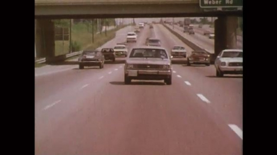 UNITED STATES: 1980s: Front view of car on highway. Title: AA Foundation for Traffic Safety. Visual Perception in Driving. Police red lights.