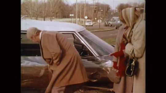 UNITED STATES: 1980s: Man looks at dent in car after accident. Policeman approaches passengers and driver. Lady talks to police man. People look at crash.