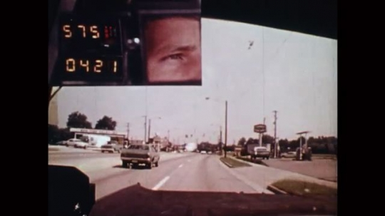 UNITED STATES: 1980s: view of man's face as he drives along busy road. Road surface and street. Arrow shows safe distance between cars. Lady drives car