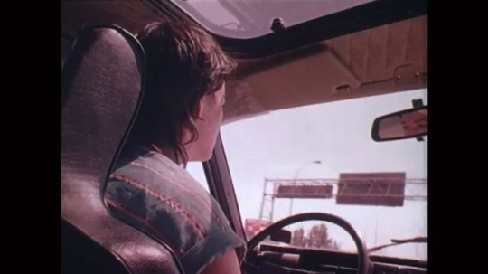 UNITED STATES: 1980s: rear view of driver in seat of car. View along road through windscreen