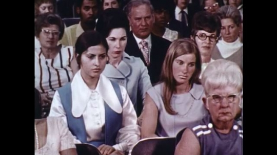 UNITED STATES: 1960s: lady in audience. Man speaks to audience.