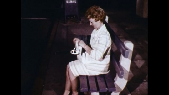 UNITED STATES: 1960s: lady sits on bench at night. Lady takes bus. Lady sits on bus at night