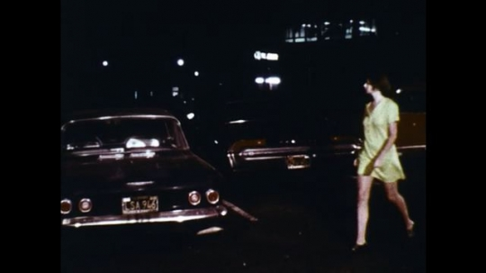 UNITED STATES: 1960s: lady walks to car at night. Lady looks in back seat.