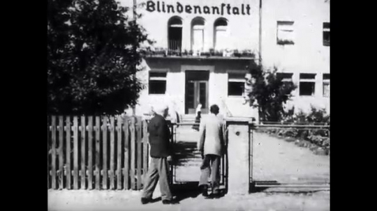 UNITED STATES: 1940s: men walk through gate of building. Home for blind people.