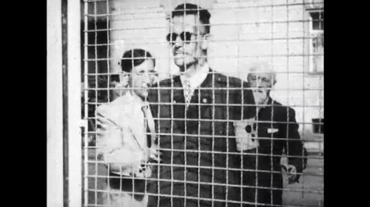 UNITED STATES: 1940s: blind man walks into wire mesh gate. Motorbikes on street. Blind man avoids vehicle. Man trips on floor.