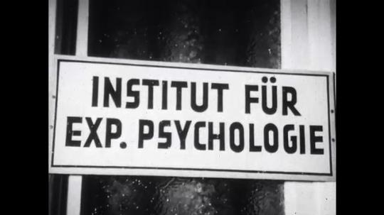 UNITED STATES: 1940s: sign for institut fur exp. Psychologie. Men guide blind man to door.