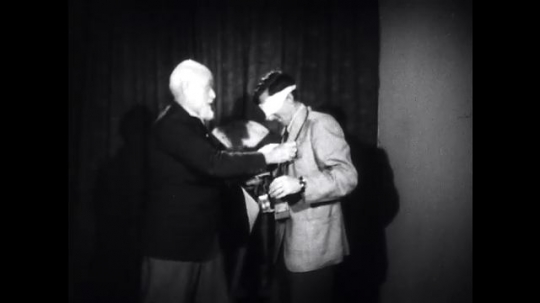UNITED STATES: 1940s: psychologist removes machine from man. Psychologist puts machine on blind man.