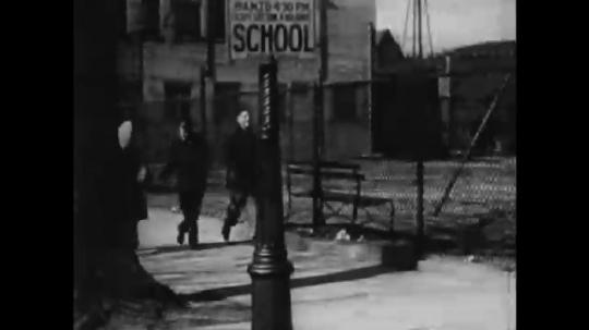 UNITED STATES: 1940s: teenagers walk to school. Boys carry ball. Hand checks lock on gate