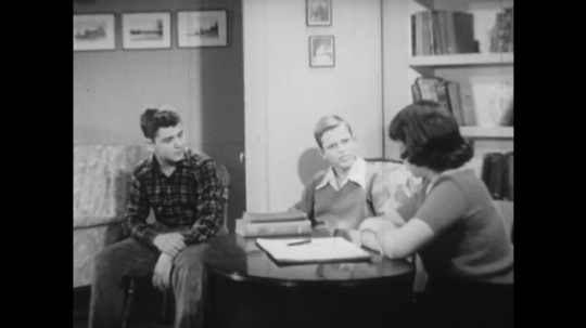 UNITED STATES: 1940s: teenagers sit in room and chat. Boy thinks to self. Children play game.