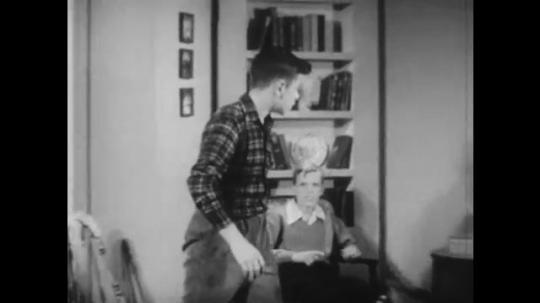 UNITED STATES: 1940s: boy stands up from chair. Boy walks over to girl at table. Boy has idea. Children talk in house. Boy picks up book