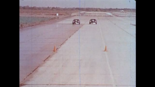 UNITED STATES: 1950s: cars drive on wet and dry surfaces in research test. View through car windscreen in rain.