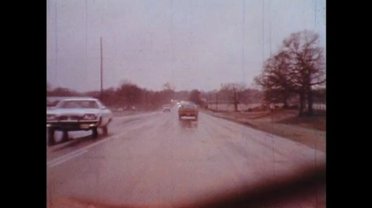 UNITED STATES: 1950s: car drives along wet road. Car research track.