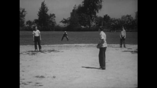 UNITED STATES: 1940s: boys on baseball pitch. Boy throws ball. Boy swings bat. Boy misses ball.