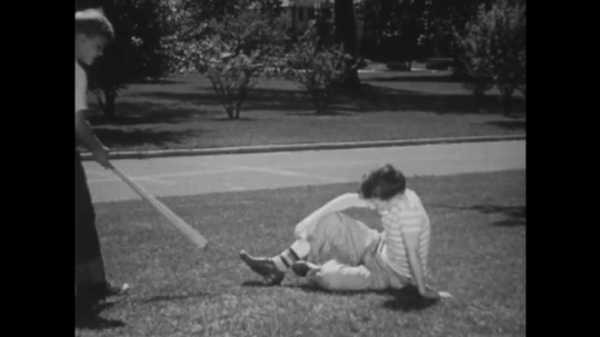 UNITED STATES: 1940s: boys talk on grass. Boy leans on baseball bat. Boy shows friend how to hold bat