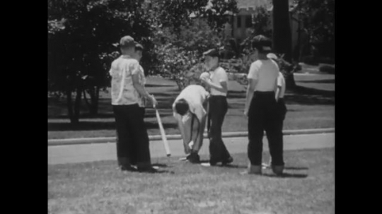 UNITED STATES: 1940s: boy straightens trousers. Boys group together during baseball game. Boy throws ball in air.