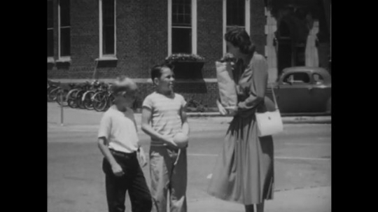 UNITED STATES: 1940s: lady talks to boys in street. Boy carries groceries for lady