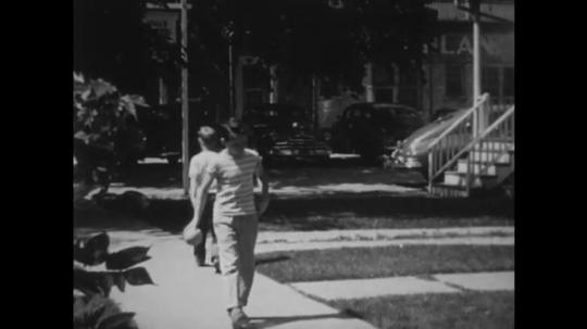 UNITED STATES: 1940s: boys say goodbye on street. Boy walks home. Boy speaks to man