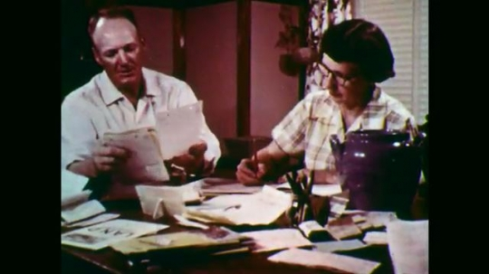 1950s: Man and woman do paperwork at table. Man milking cow. Close up of dog. Man hammers roof. Man welding.
