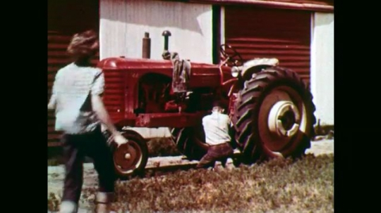 1950s: Boy working on tractor, girl approaches. Boy talks to girl in foreground. Close up, girl talking. Girl walks away. Pan of young people in audience.