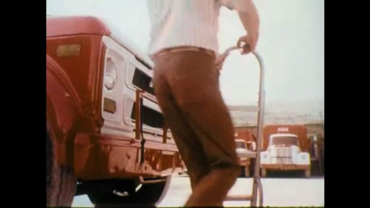 1970s: Man pushes hand truck, attaches to truck grill. Man gets in to truck. Truck drives past camera, Coke logo on building.