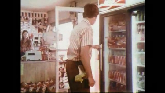 1970s: Man opens display case, picks up cans. Truck stops by road stand. Man talks to man at road stand. Close up, man talking.