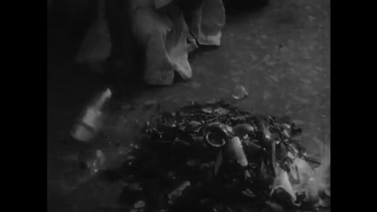 AFRICA: 1930s: street entertainer smashes glass bottles with foot and walks in shards.