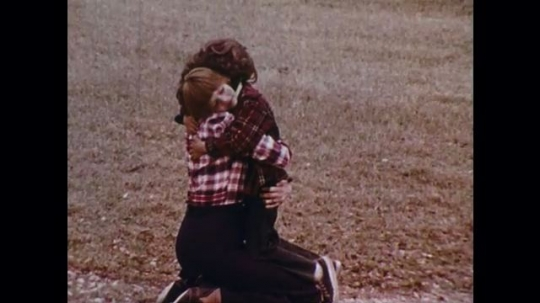 UNITED STATES: 1970s: lady hugs lost boy. Police officers at work. Men march. Cars on street