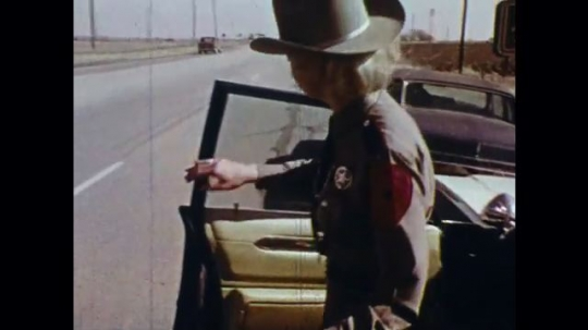 UNITED STATES: 1970s: Police Trooper stops car driver. Texas Highway Patrol car. Texas Rangers.