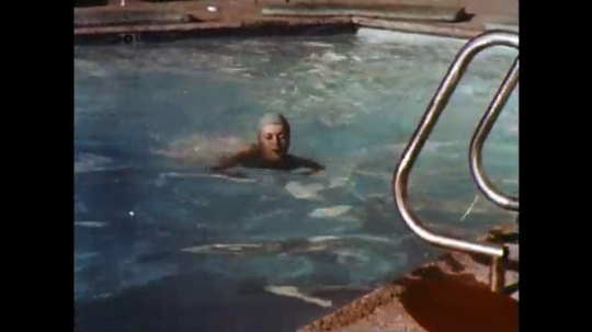 UNITED STATES: 1960s: lady swims in outdoor pool. Lady walks dog outdoors.