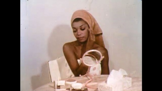 UNITED STATES: 1960s: lady looks in mirror and puts on make up.